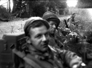 Dad in helmet, George Nelson in foreground. On patrol near Ste. Mere Eglise, shortly after D-Day. Often two radio operators worked together and one could operate the radio while the other carried it, plus the second operator could carry additional batteries.
